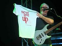 """Il chitarrista Cico Falzone mostra dal palco la t-shirt """"Never Give Up"""" dedicata all'evento """"Anno del Dalai Lama"""""""