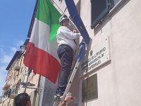 Mario Ferrari mentre sostituisce la bandiera italiana
